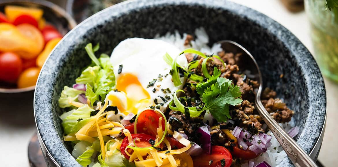 Okinawa Taco Rice in a stone bowl topped with lettuce, cheese, tomatoes, cilantro, and a poached egg.