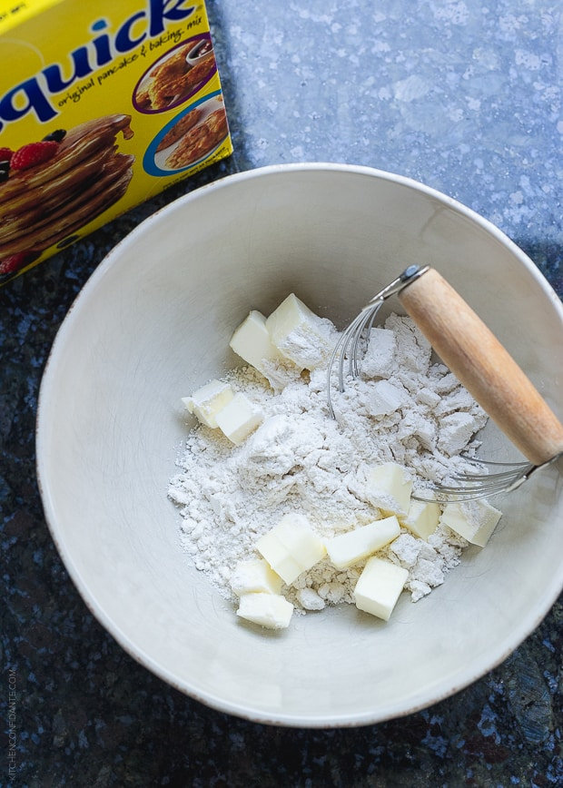 Flour and small squares of butter in a bowl with a pastry cutter.