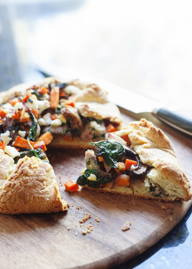 A Savory Chicken Sausage and Vegetable Galette with a slice removed on a wooden serving board.