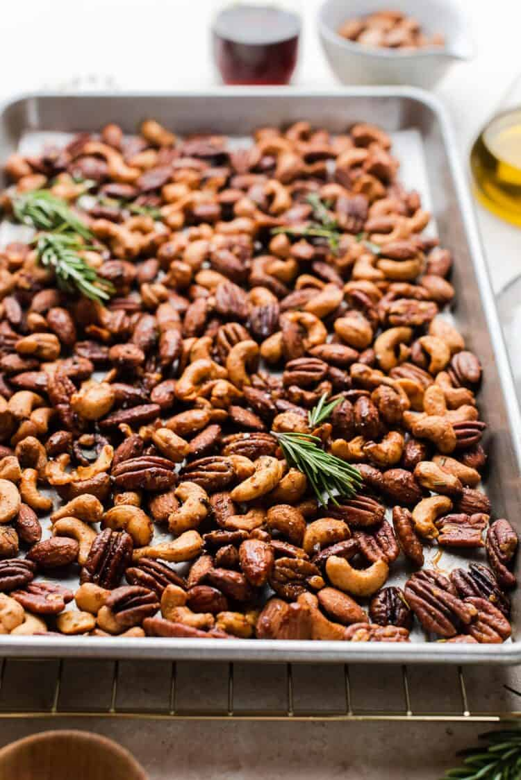 A baking sheet with spiced nuts and herbs.