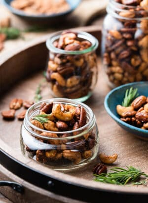 Spiced nuts in mason jars on a wooden tray.
