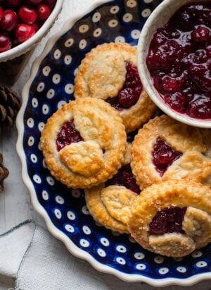 Cranberry Hand Pies in a blue ceramic pie dish with a bowl of cranberry sauce on the side.