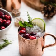 Pomegranate Cranberry Moscow Mule in a copper cup garnished with cranberries, mint, lime and rosemary.