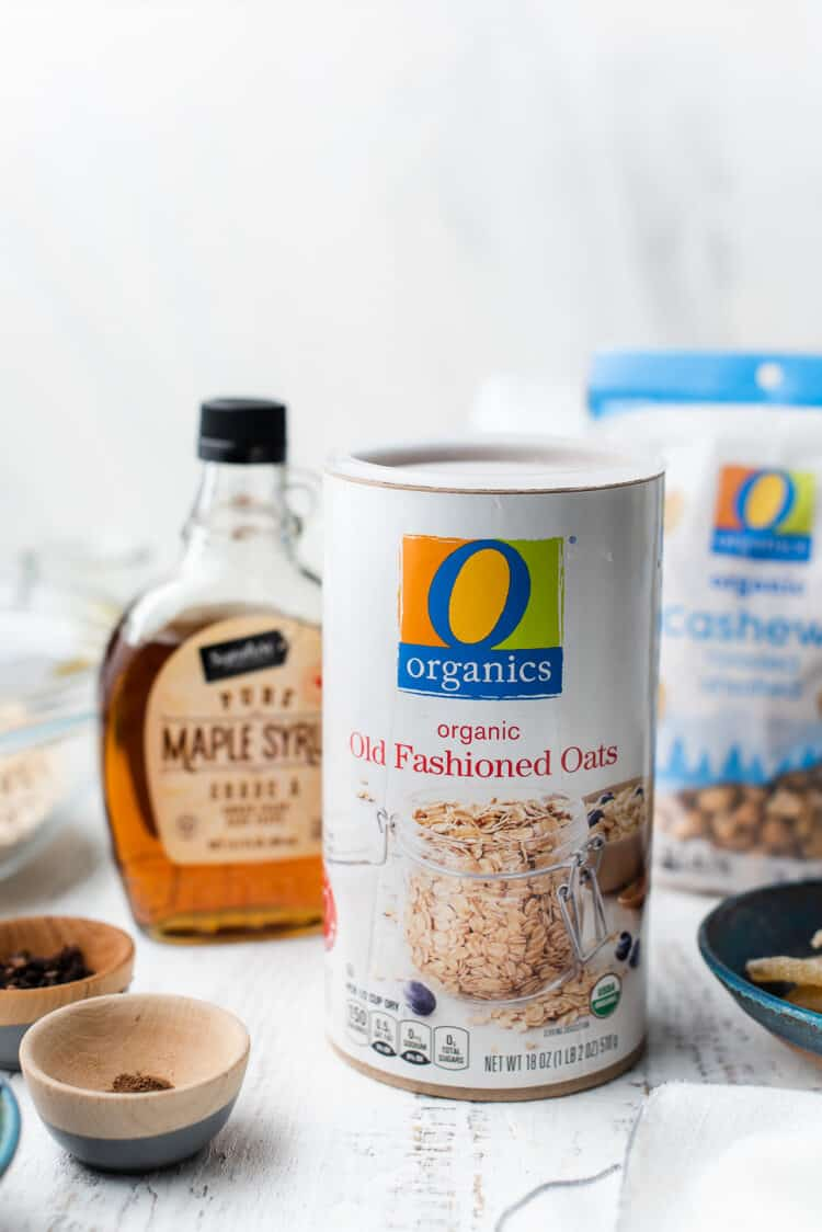 O Organics Oats with maple syrup and cashews for Gingerbread Granola on a white table.