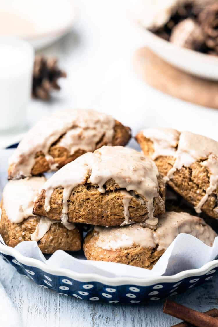 Gingerbread Scones with Gingerbread Maple Glaze on a parchment lined dish.