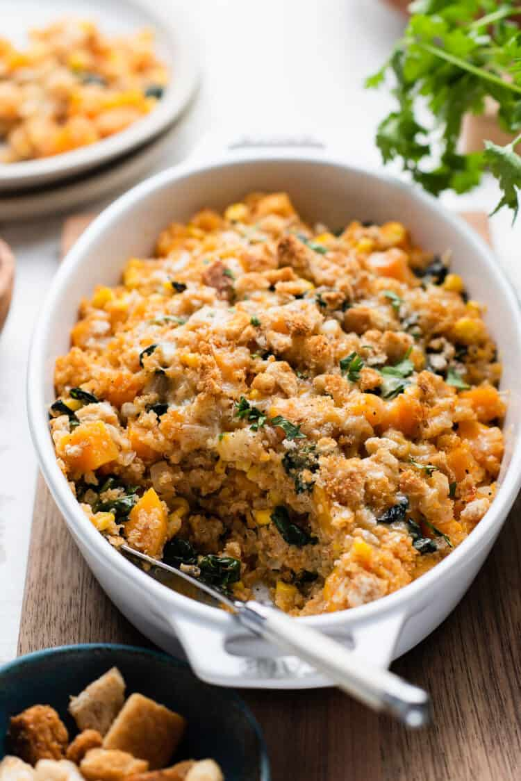 Winter Squash and Quinoa Bake in a baking dish with a serving spoon