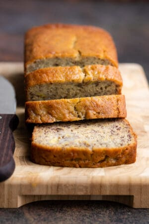 A loaf of the best moist banana bread recipe sliced on a wooden cutting board.