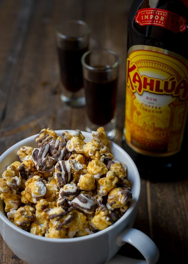 A mug of caramel corn with a bottle of Kahlúa nearby.