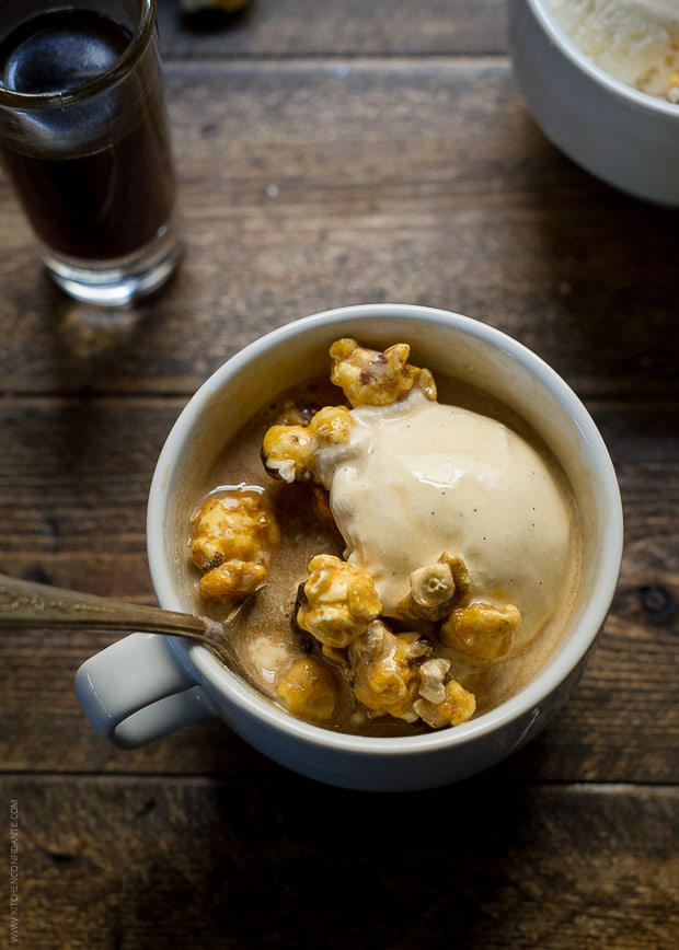 A white mug filled with expresso, vanilla ice cream, caramel popcorn, and a shot of Kahlua.