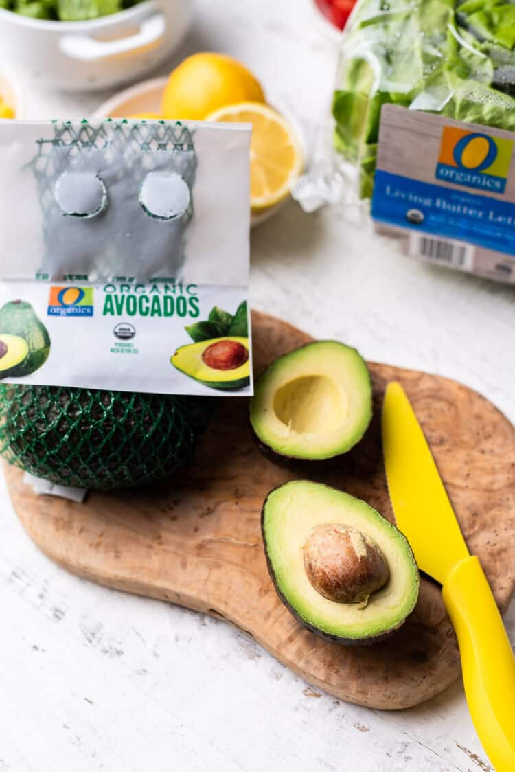 O Organics avocados for chicken cobb salad on a wood cutting board.