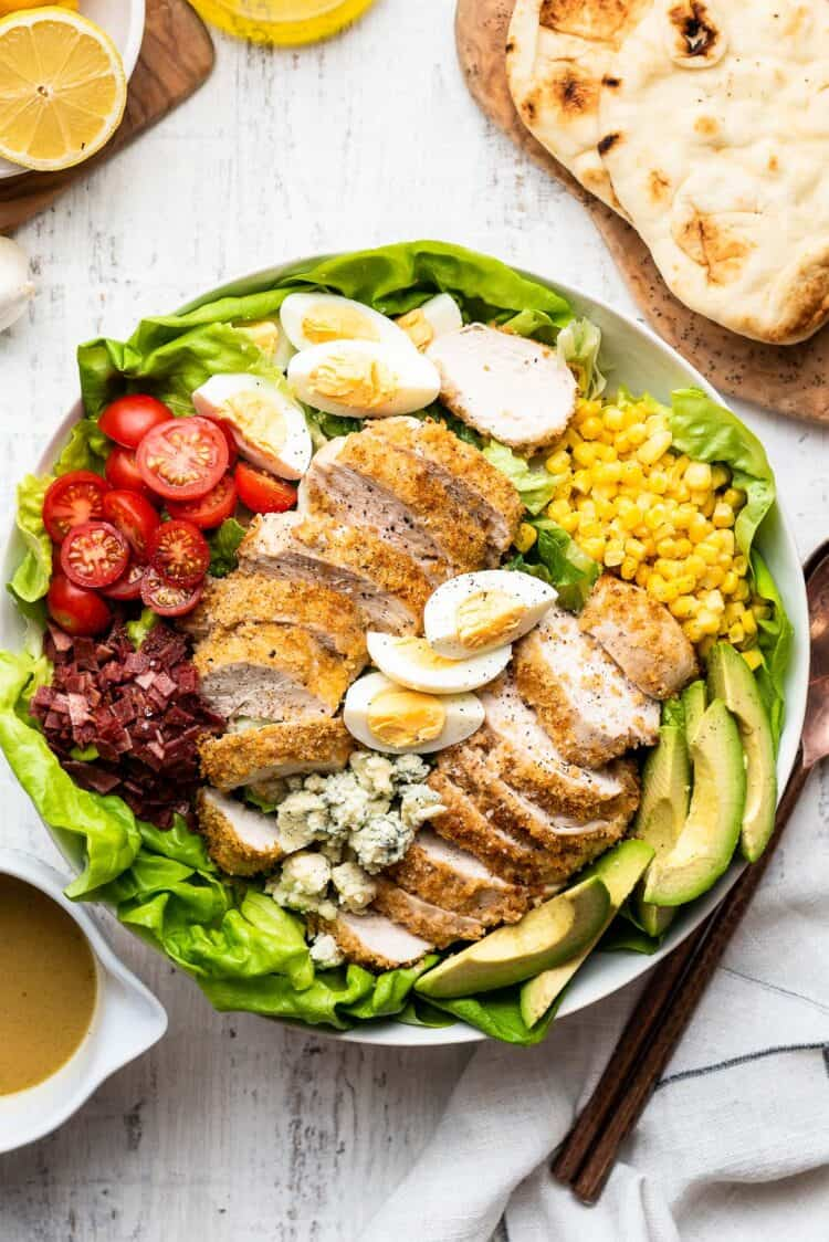 Crispy Chicken Cobb Salad in a white bowl with dressing on the side.