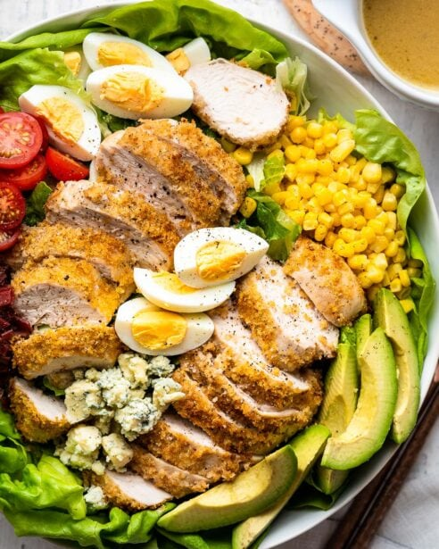 Crispy chicken Cobb salad in a white round bowl with air fryer breaded chicken, hard boiled eggs, avocado, tomato , bacon, corn, blue cheese and lettuce with Cobb salad dressing on the side.