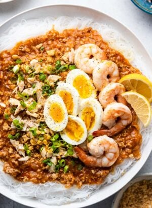 Pancit Palabok in a white bowl garnished with shrimp and hard boiled eggs.