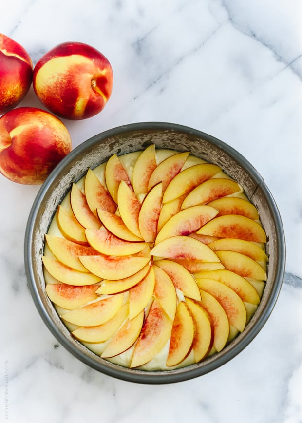 Sliced nectarines arranged on top of a cake ready to be baked.
