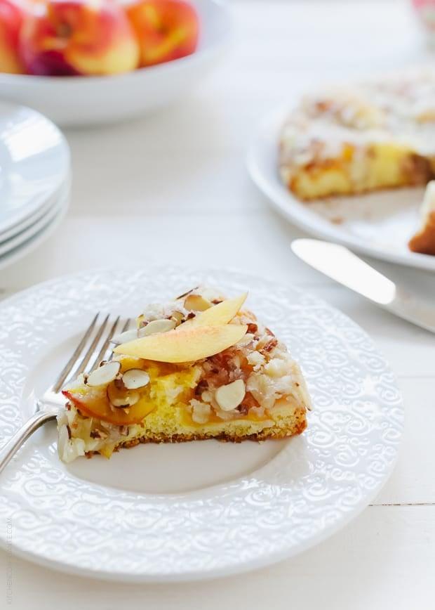 A slice of Nectarine Crumb Cake on a white plate.