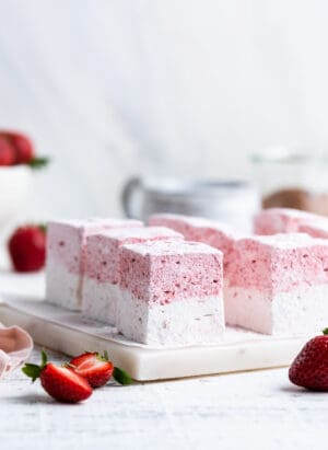 Homemade Strawberry Vanilla Marshmallows sliced on a white marble cutting board.