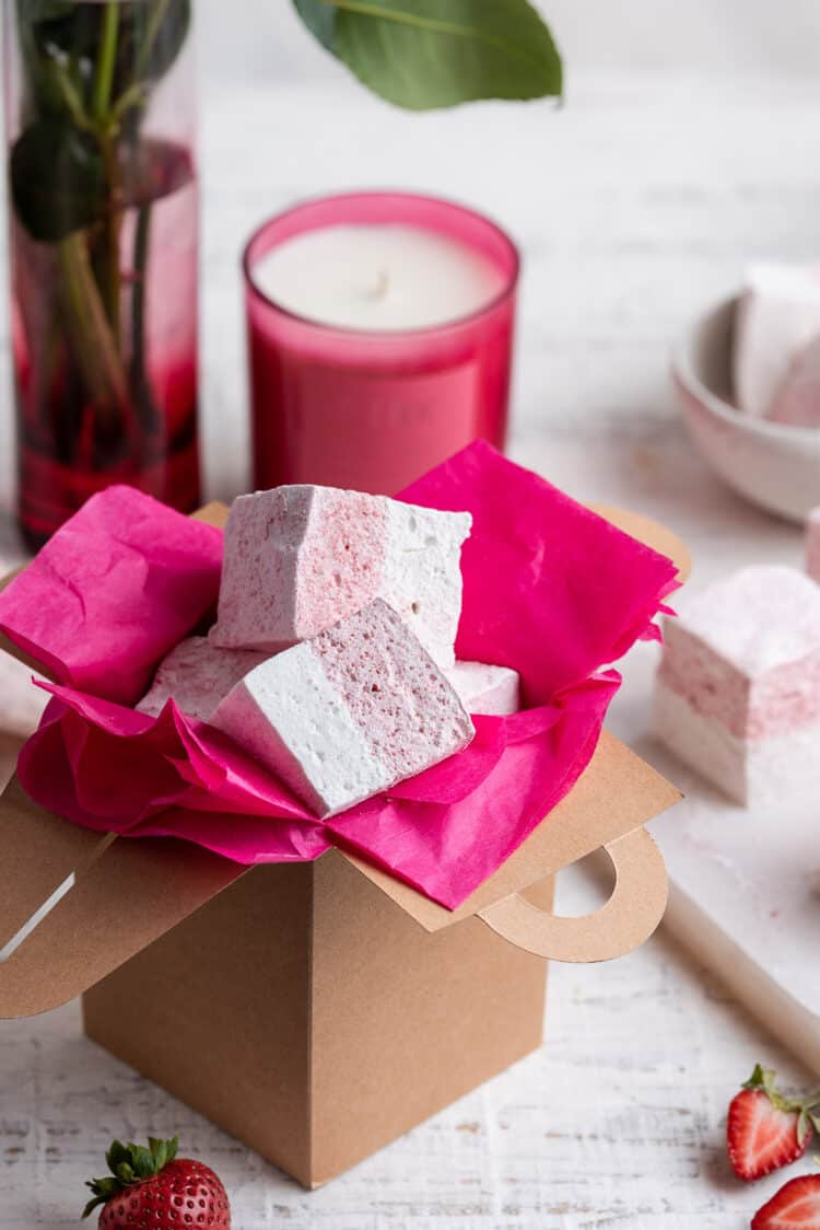 Homemade Strawberry Vanilla Marshmallows in a gift box lined with pink paper for gifting.