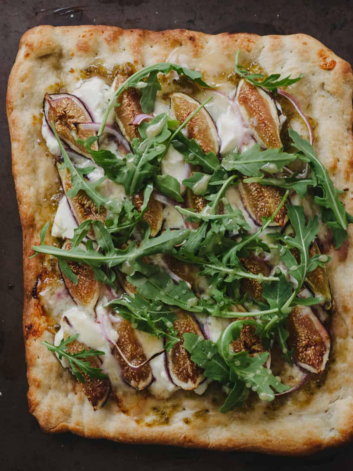 A homemade Fig, Jalapeño Jam & Blue Cheese Pizza topped with fresh arugula.