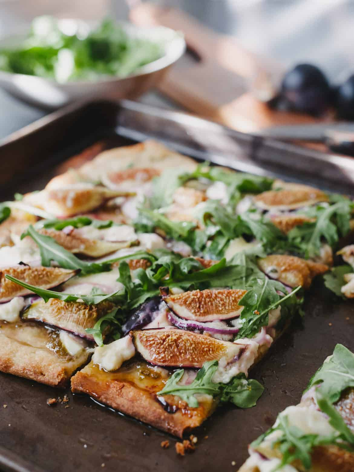 Homemade pizza topped with slices figs, fresh arugula, and blue cheese on a baking sheet.