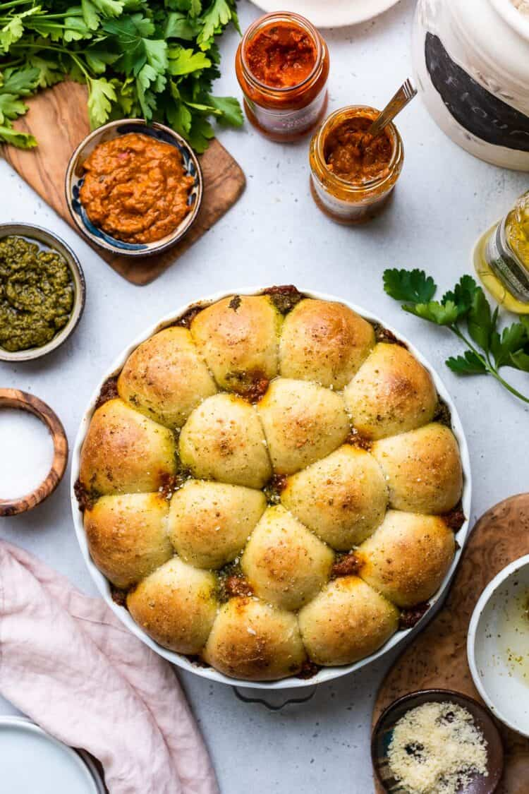 Pesto Pull-Apart Rolls in a white baking dish with pestos on the side.