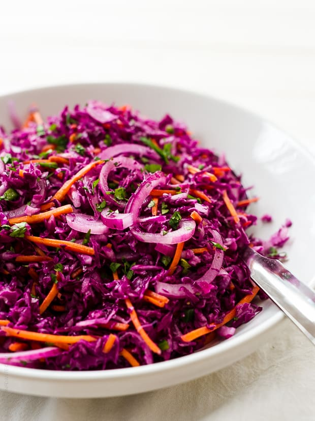 Shredded cabbage slaw in a white bowl.
