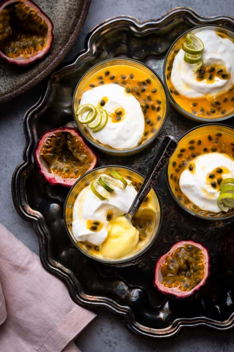 Passion Fruit Possets on a serving tray with fresh passion fruit topping.