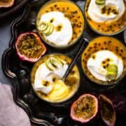 Passion Fruit Possets on a tray topped with coconut yogurt and a garnish of lime peel.