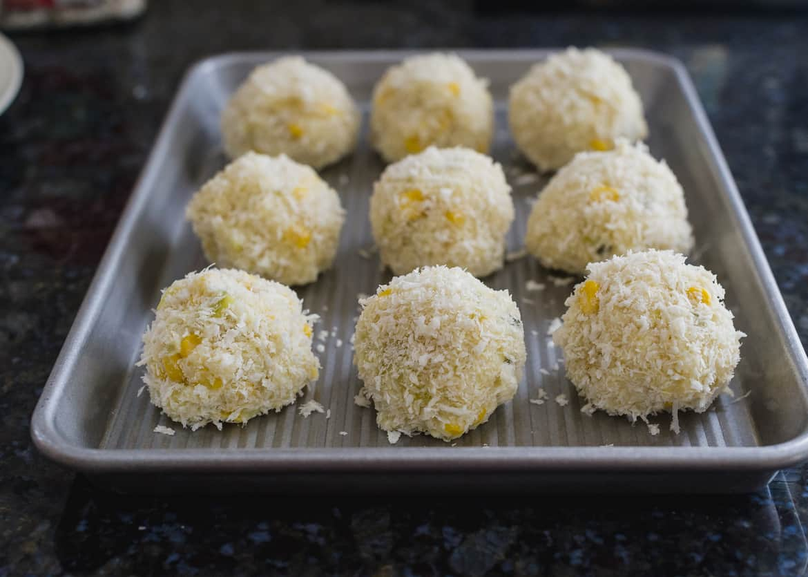 Jalapeño, Corn and Cheddar Arancini arranged on a tray, ready to be fried.