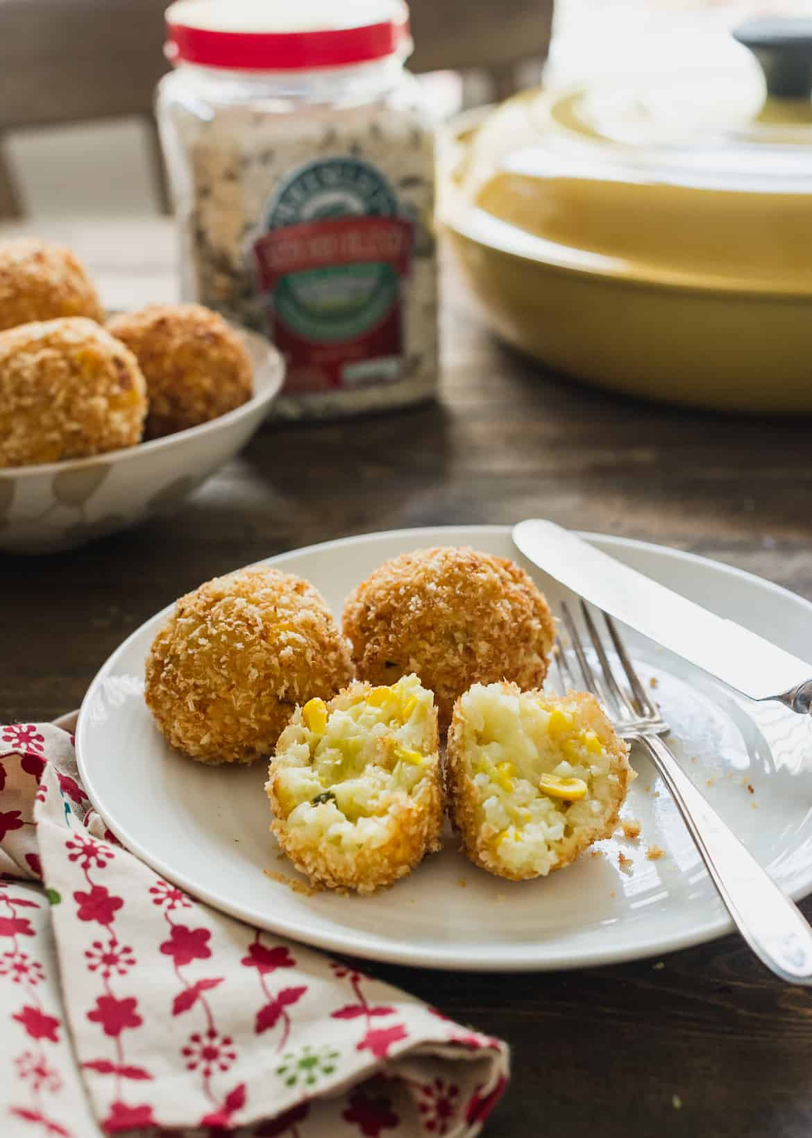 Jalapeño, Corn and Cheddar Arancini split open and served on a plate.