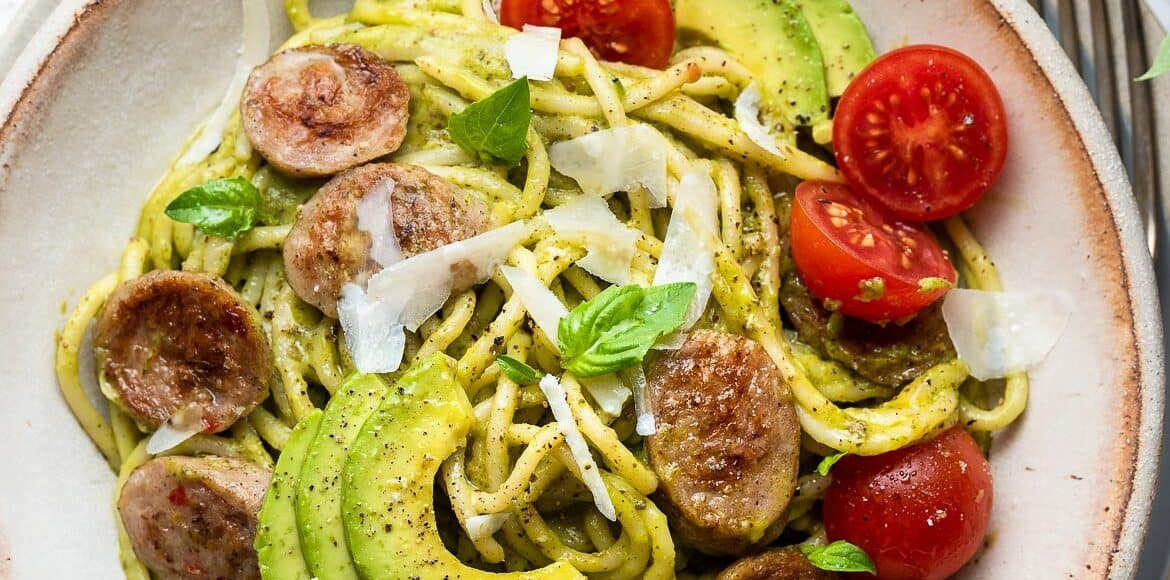 Avocado Pesto Pasta with Chicken Sausage with tomatoes, basil, and parmesan cheese.