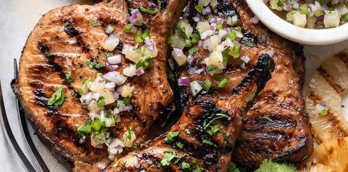 Grilled Pineapple Pork Chops on a platter with grilled pineapple and pineapple salsa.