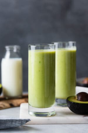 Avocado milk smoothie in two tall glasses.