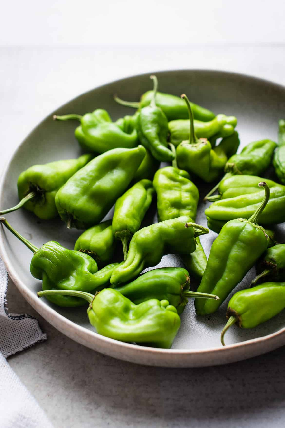 Green Padrón Peppers on a large plate.