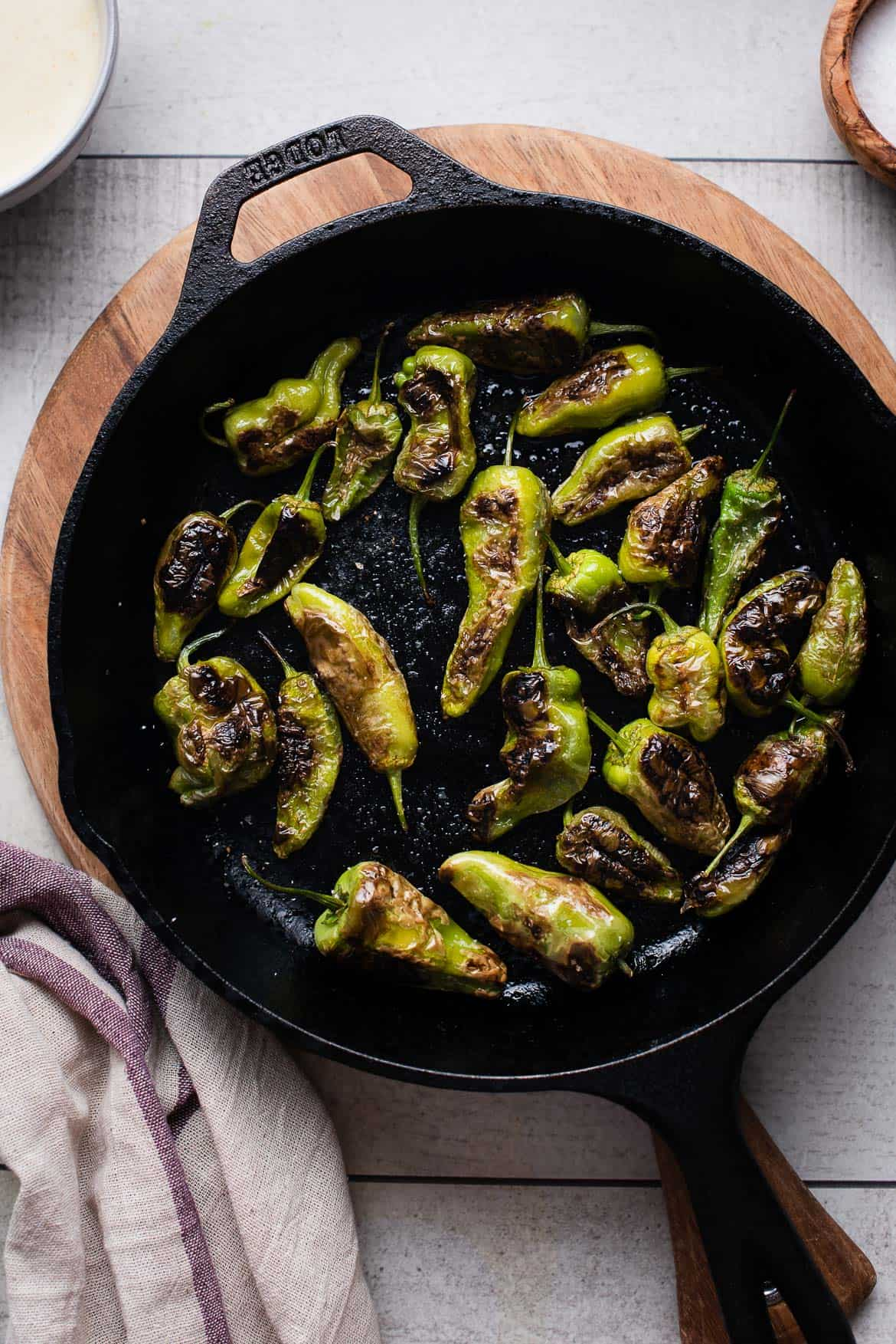 Blistered Padrón Peppers in a cast iron pan.