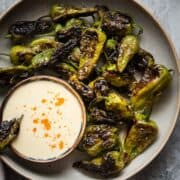 Blistered Padrón Peppers served with a bowl of Buttermilk Aioli.