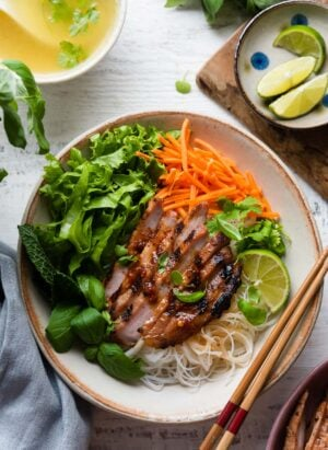 Vietnamese-style Grilled Pork Chops in a bowl on a bed of rice noodles and vegetables.