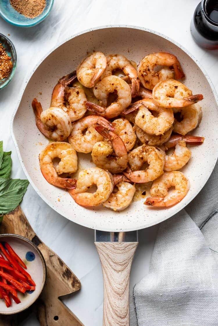 Thai-style shrimp in a white skillet.