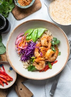 Thai-style Shrimp Bowls with brown rice, red cabbage, red onions, carrots, and snow peas served with Spicy Coconut Dressing on the side.